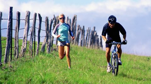 A man and woman exercise outdoors.