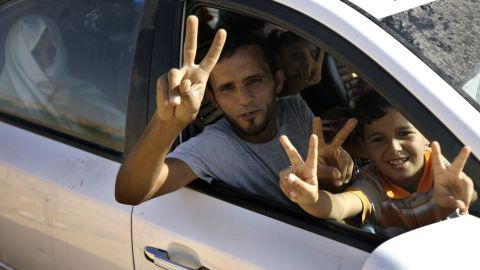 Libyan civilians flash the victory sign at a Bani Walid checkpoint controlled by new regime fighters on September 13.