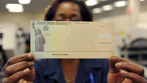 An employee holds a blank check before it's run through a printer at the U.S. Treasury printing facility in Philadelphia.