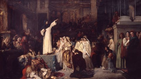 """Savonarola warned of the risks of wealth and ostentation. Ludwig von Langenmantel's 1881 painting """"Savonarola Preaching Against Luxury and Preparing the Bonfire of the Vanities,"""" imagines him as a lone, austere figure standing up to a decadent world."""