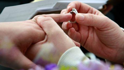 Jodie Vandermark-Martinez slides a ring on her partner Jessice during their wedding ceremony in Iowa.
