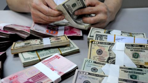 A staff member counts money at a branch of the Bank of China on August 10 in Lianyungang, Jiangsu Province of China.