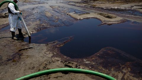 Crews suck up oil from the Deepwater Horizon disaster in Grand Isle, Louisiana, on June 9, 2010.