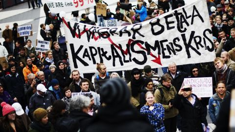 """Protesters hold a banner that says in Swedish, """"We refuse to pay the crisis of capitalism,"""" as they take part in the Occupy Stockholm demonstration on Saturday."""