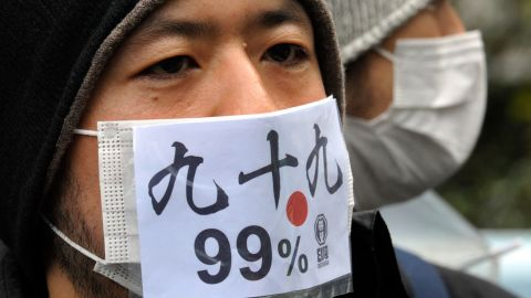 """A Japanese protestor wears a mask that says """"we are 99 percent"""" during a Saturday protest in Tokyo."""