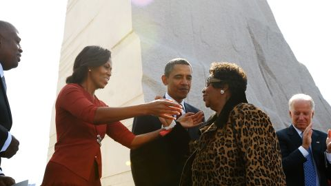 """First lady Michelle Obama, left, reaches out to embrace singer Aretha Franklin as President Obama , Vice President Joe Biden, and Jill Biden look on after Franklin performed at the ceremony. Franklin sang """"Take My Hand, Precious Lord,"""" a song she said King often requested."""