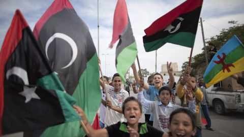 """Libyan children wave NTC flags in Tripoli. """"Libya is now under the full control of National Transitional Council forces,"""" Catherine Ashton, the European Union foreign policy chief, said Thursday."""