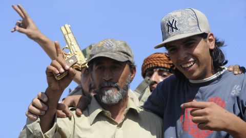 Anti-Gadhafi fighters hold what they say is the gold-plated gun of the ousted leader in Sirte, Libya, last week.
