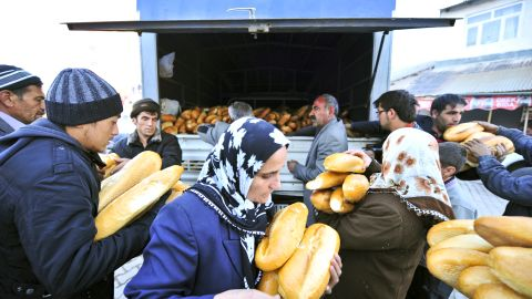 Ercis residents collect loaves of bread provided by relief agencies on Monday.