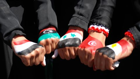 Yemeni women show off their fists painted in the colors of five Arab national flags (l to r):- Yemen, Libya, Syria, Tunisia, Egypt.