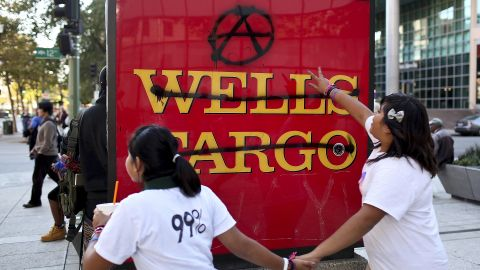 Protesters run by a defaced Wells Fargo bank sign during Occupy Oakland's general strike. Wednesday's incidents involved graffiti and smashed windows, police say.