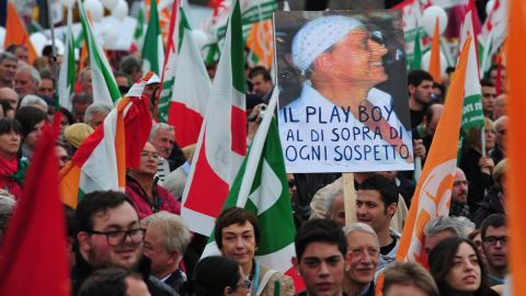 """Demonstrators hold a placard with a portrait of Italian Prime Minister Silvio Berlusconi and reading """"The playboy above suspicion"""" during a protest Saturday in Rome"""