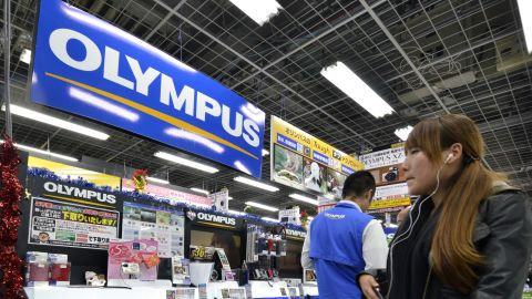 A customer looks at the Olympus booth at a camera shop in Tokyo on November 10.