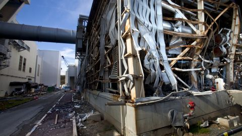 The crippled Fukushima Daiichi nuclear power station is visible through a bus window Saturday.