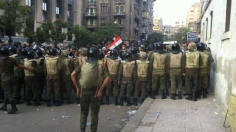 Egyptian military act as a buffer between police and protesters.