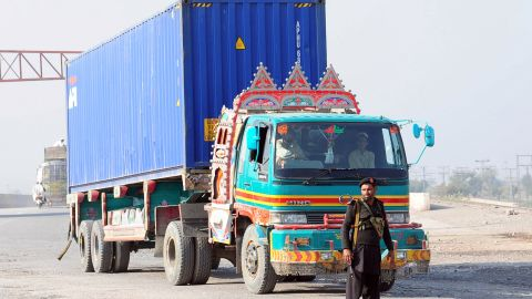 Pakistani security personnel watch a truck carrying supplies for NATO forces in Afghanistan return from Pakistan's Torkham border crossing after Pakistani authorities suspended NATO supplies on November 26, 2011.
