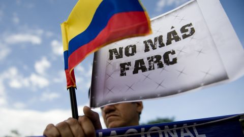 """A man holds a Colombian flag with a sign that reads """"No more FARC"""" on Wednesday, November 23, in Cali, Colombia."""