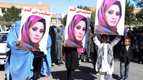 Activists in Herat hold portraits of Semin Barakzai to protest her unseating in the  Afghan parliament over vote-rigging allegations.