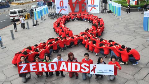 Dozens of volunteers join a human chain in the form of a red ribbon in Taiwan for World AIDS Day 2011.