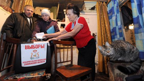 A woman casts her ballot for Russian parliamentary elections in the box local election officials brought to her village home.