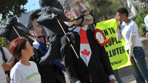 An environmental activist wears a mask depicting Canadian Prime Minister Stephen Harper in Durban, December 5.