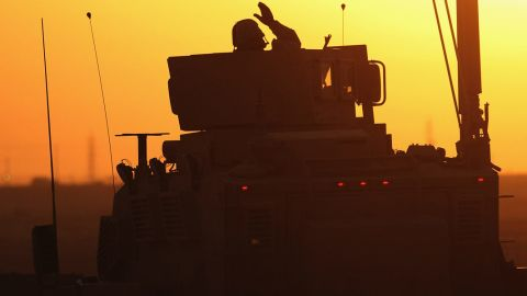 A soldier in the last American military convoy to depart Iraq, from the 3rd Brigade, 1st Cavalry Division, waves after crossing into Kuwait on December 18, 2011.
