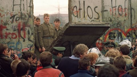 West Berliners crowd in front of the Berlin Wall on November 11, 1989, as they watch East German border guards demolishing a section of the wall in order to open a new crossing point between East and West Berlin.