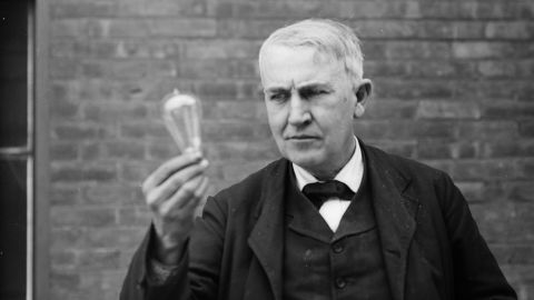 Inventor and physicist Thomas Alva Edison looking at a light bulb
