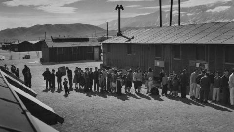 UNITED STATES - CIRCA 1943: People of all ages wait in a line in front of a building at midday. Ansel Easton Adams (1902  1984) was an American photographer, best known for his black-and-white photographs of the American West. During part of his career, he was hired by the US Government to record life in the West.