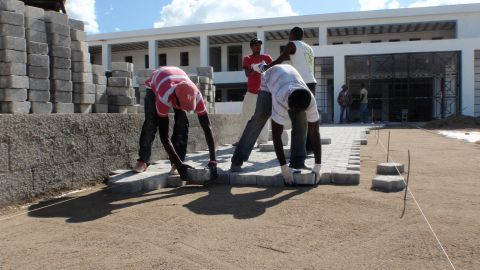 Local workers lay paving stones at the front entrance to Mirebalais National Teaching Hospital in Haiti. The hospital will open this year and boasts a neonatal intensive care unit and six operating rooms that can handle thoracic surgery.