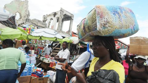 Haitian vendors sell their goods in Port-au-Prince amid earthquake-damaged buildings. The United Nations says 50% of the rubble left by the January 12, 2010, earthquake still litters the Haitian capital.