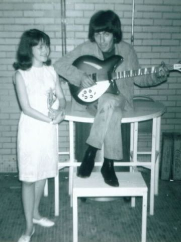 Kordus joins George Harrison while he tunes a guitar in the shower room backstage.