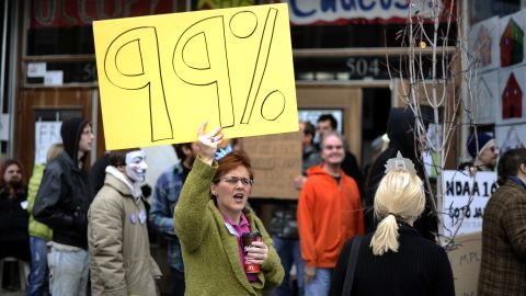 """Activists of """"occupy Iowa caucuses"""" shout slogans as they march along a street in Des Moines, Iowa, on December 31."""
