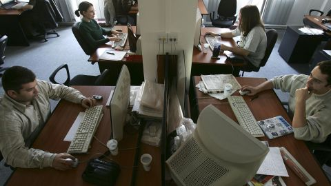 Young programmers work at an IT company in Romania, where thousands of college graduates enter the tech field yearly.