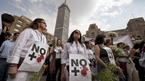 """Anti-violence activists protest in Mexico City in April 2011. Their signs read, """"No more blood."""""""