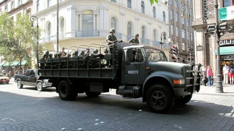A truck carries troops through the historic center of Mexico City, where major cartel violence has not been a part of daily life.