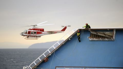 """Firemen work on the Costa Concordia cruise ship on January 16. The captain may have made """"significant"""" errors that led to wreck, the cruise line said."""