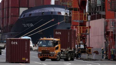 Containers are loaded and unloaded from a container vessel at a Tokyo port on November 21, 2011.