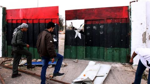 On Wednesday, Libyan men stand at the destroyed gates at a military base damaged during earlier fighting in Bani Walid.