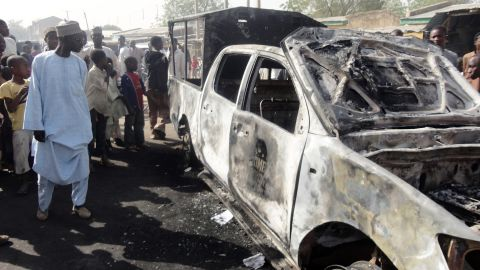 A resident inspects a police patrol van outside Sheka police station in northern Nigerian city of Kano on January 25, 2012. The van was burnt in bomb and shooting attacks on the police station the previous night by around 30 members of Boko haram Islamists group, wounding a policeman and killing a female visitor, according to residents. AFP PHOTO / AMINU ABUBAKAR (Photo credit should read AMINU ABUBAKAR/AFP/Getty Images)