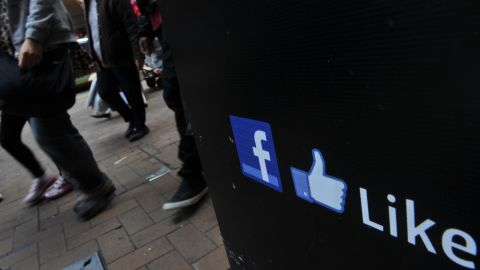 People walk by a Facebook logo and a thumbs up logo made popular by Facebook in Hong Kong on February 2, 2012.