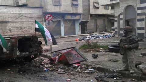 A Syrian rebel stands next to a destroyed government forces tank bearing the rebel-adopted revolution flags in Homs.