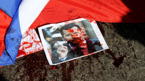 A picture of Syria's embattled President Bashar al-Assad sprayed with red paint lies on the ground next to a Russian flag about to be set on fire by protesters opposed to the Syrian regime during a demonstration outside the Russian embassy in Beirut on February 5.