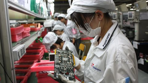 File photo workers on a production line at Foxconn's Longhua plant in Shenzhen, which employs 300,000.