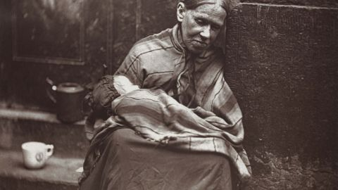 Dickens' work often focused on extreme poverty; here, a photo from an 1877 book on London street life shows a destitute mother sitting with her infant on stone steps.