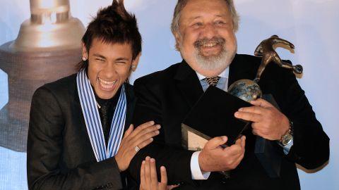 Brazilian football player Neymar (L) celebrates with the president of Brazilian club Santos, Luis Alvaro de Oliveira,