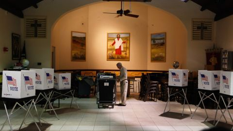 A worker sets up a polling station the morning of the GOP primary in Florida. Fewer voters than expected turned out.