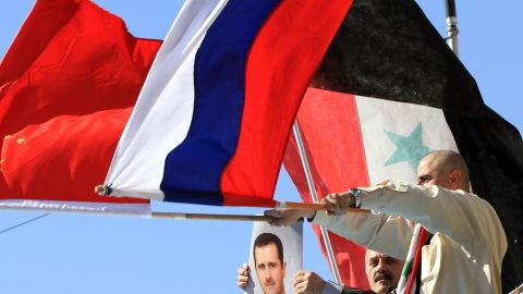 Supporters of Syria's president wave Russian, Chinese and Syrian flags during a pro-regime rally in central Damascus.