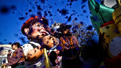 Revelers throw confetti to the public in the annual carnival parade in Loule on Saturday.