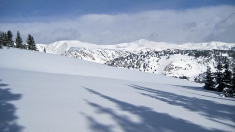 A pristine mountainside of fresh powder begs to be skied in the Colorado backcountry.